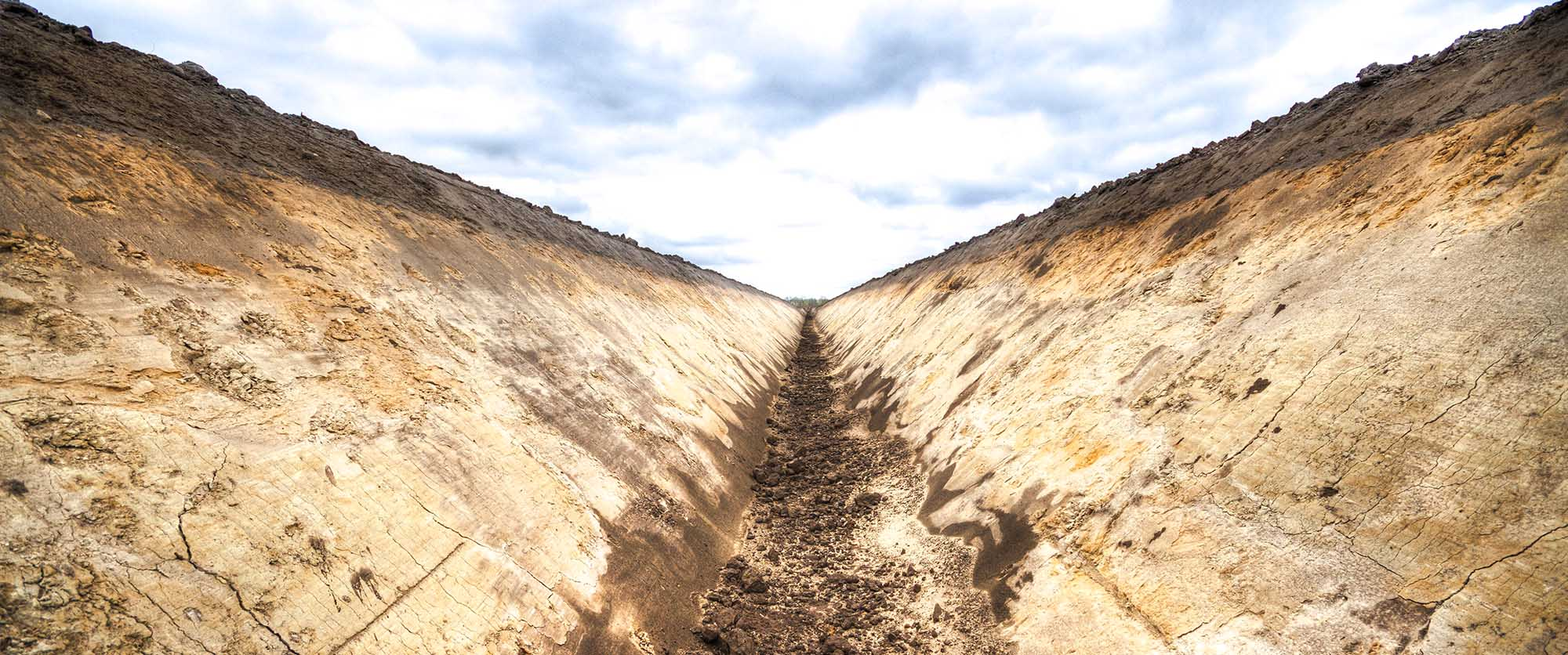 Freshly dug field drainage ditch showing soil stratification under a sky with dark clouds